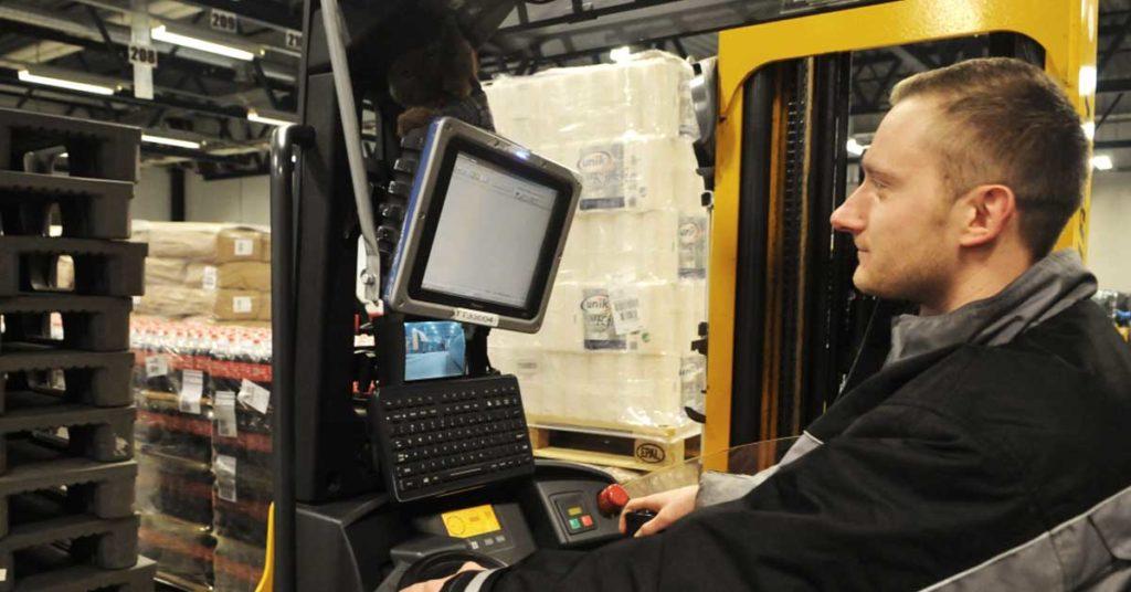 En mann som sitter i en truck på et lager og ser på en skjerm