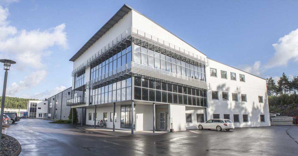 Et stort hvitt bygg med parkeringsplass foran