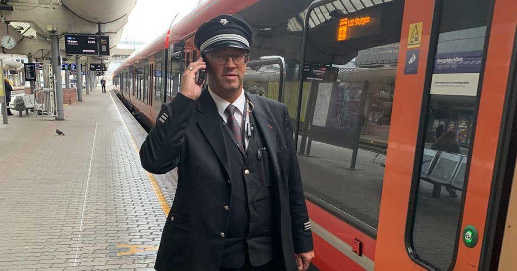 En konduktør som prater i telefon utenfor et tog