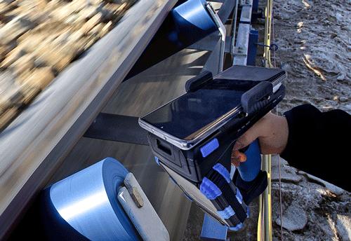 Håndterminal ved siden av en maskin som håndterer stein
