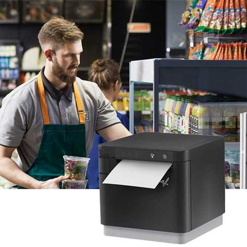 En mann som jobber i kiosk og et bilde av en printer