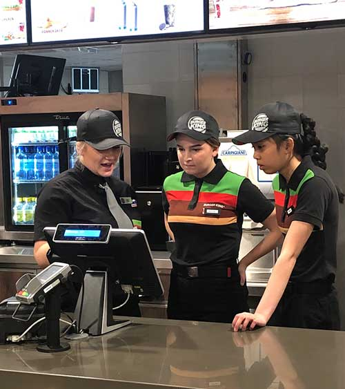 Tre mennesker foran en skjerm i en restaurant