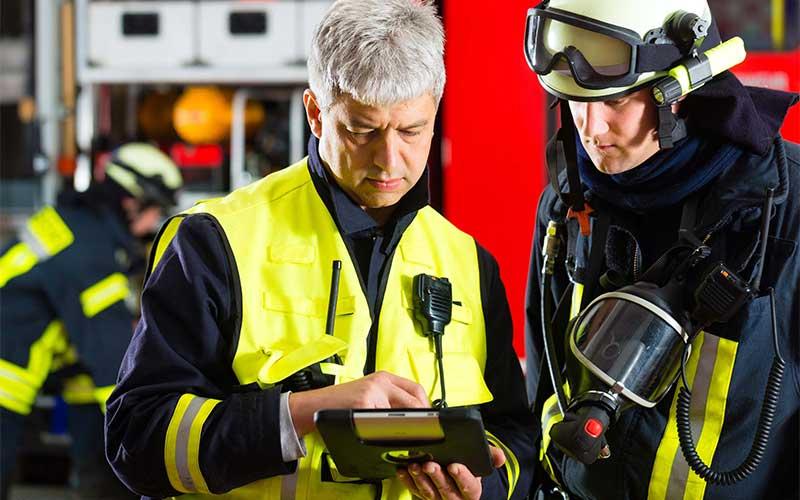 brann og redningsmannskap taster på en skjerm