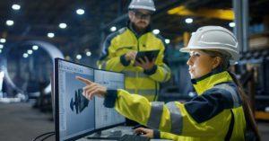 to industriarbeidere ved pc-skjermer og nettbrett