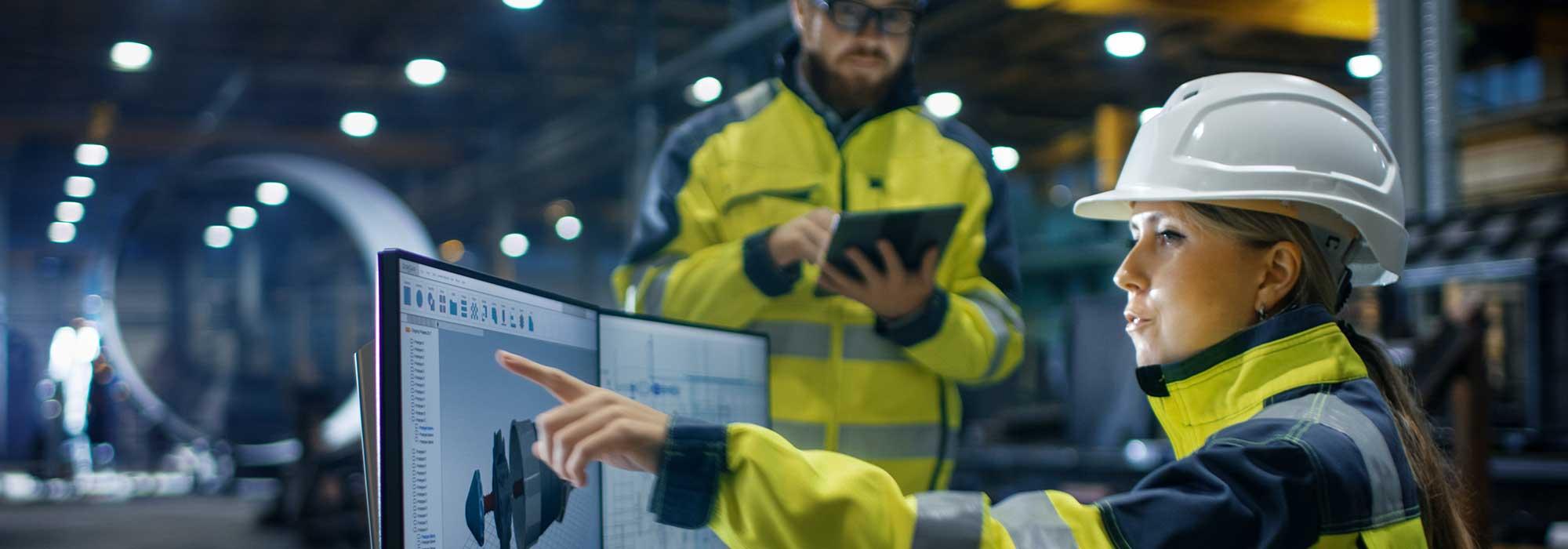to industriarbeidere sitter ved en skjerm og holder et nettbrett